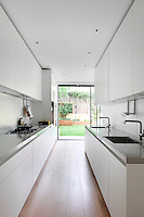 A spacious white galley kitchen with a sliding glass door leading to the garden.