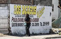 Un hombre indigente , camina sobre la acera junto a una publicidad del restaurante Los Magos<br /> Pobreza, Abadono, sin casa, no home, homless.