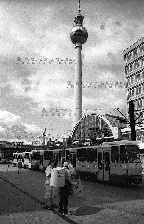 berlino, quartiere mitte. venditore ambulante di hot dog in alexander platz e la torre della televisione (fernsehturm)--- berlin, mitte district. a hot dog hawker in alexander platz and the television tower (fernsehturm)