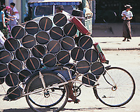 The hat of the rickshaw driver is just visible above the load of piping which he is transporting through the streets of Pegu in Burma.
