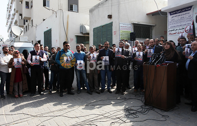 Palestinian journalists hold posters depicting Palestinian journalist Yasser Murtaja, 30, who was killed by Israeli security forces during clashes with Palestinian protesters, in a press conference outside al-Shifa hospital in Gaza city on April 7, 2018. Photo by Mahmoud Ajour