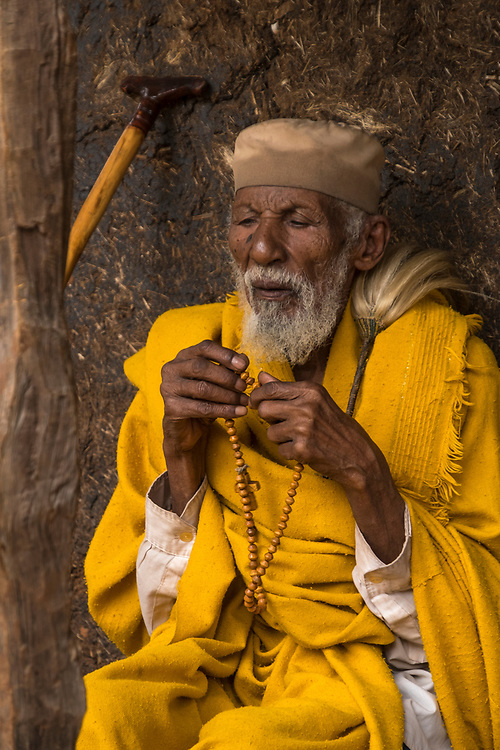 Seemingly unaware of his immediate surroundings, this aged priest spends his devotion time manipulating prayer beads.