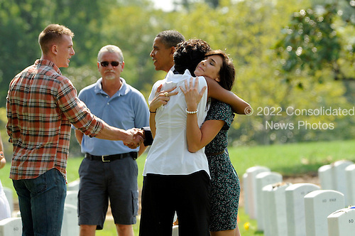 First Lady Michelle Obama hugs an unidentified woman as she and United States President Barack Obama visit Section 60 at Arlington National Cemetery, on Saturday, September 10, 2011, in Arlington, Virginia.  This section contains military personnel who were killed in the Iraq and Afghanistan wars since 9/11. .Credit: Leslie E. Kossoff / Pool via CNP