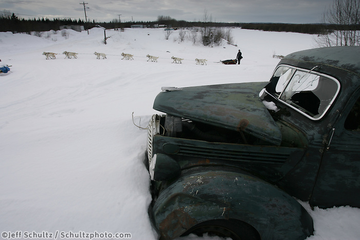 Jim Lanier drives his team by an old abandoned Ford pickup as he arrives at the Anvik checkpoint. 2005 Iditarod Trail Sled Dog Race.
