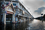 Local residents paddle towards a temple in western Bangkok.<br />