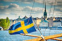 Svensk flagga på en träbom vid Strandvägen med utsikt över Gamla stan i Stockholm