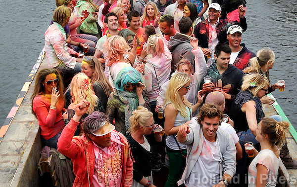 Leidse Lakenfeesten. Peurbakkentocht door de grachten. Jongeren zijn bestrooid met gekleurd poeder.