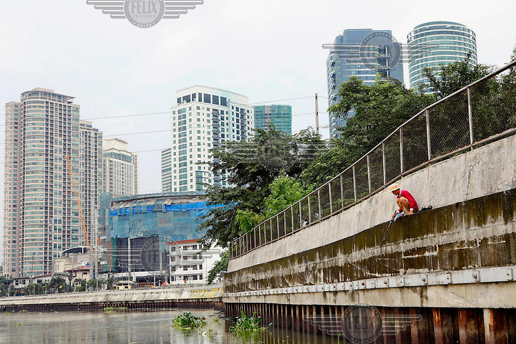 A man, perched on a narrow ledge on the side of a concrete water defence, tries his luck fishing in the heart of Manila.