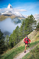 A woman trail running above Zermatt, Switzerland with a view of the Matterhorn.