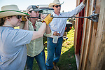 The Busi family and friends use hot irons to christen and brand the new pump shed at their corrals near Jackson, California.<br /> <br /> Kelsi Busi makes the first brand as her mother Colett helps and friend Seth Seever watches