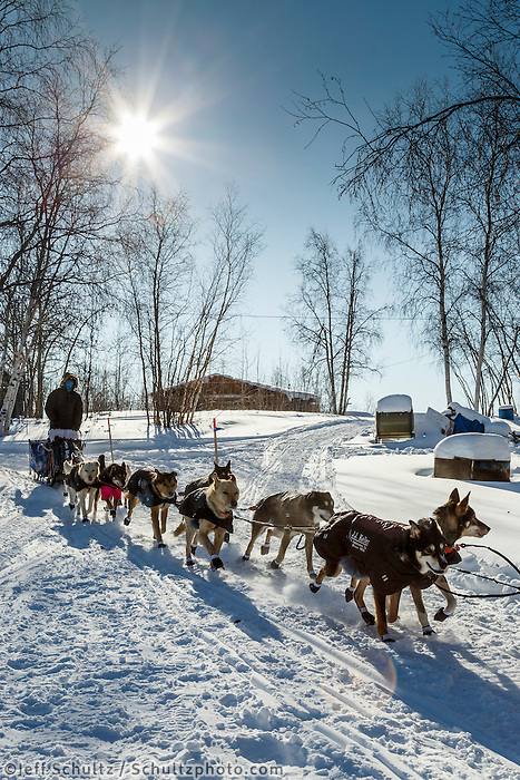 Christian Turner runs down the trail past houses in the afternoon as he leaves the Huslia checkpoint on Saturday  March 14, 2015 during Iditarod 2015.  <br /> <br /> (C) Jeff Schultz/SchultzPhoto.com - ALL RIGHTS RESERVED<br />  DUPLICATION  PROHIBITED  WITHOUT  PERMISSION