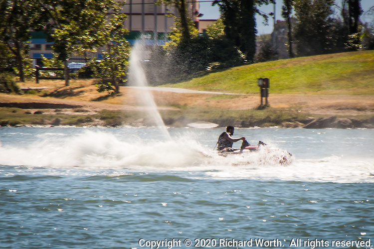 A visitor to the MLK Regional Shoreline near Oakland, California's airport does donuts in the water on his jet ski.