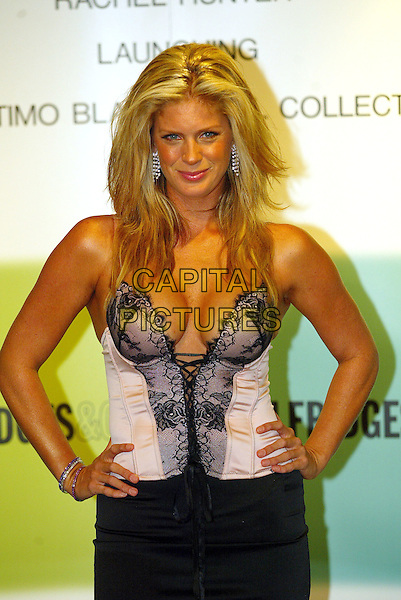 RACHEL HUNTER.Ultimo Launch of Autumn/Winter 2004 Collection in Selfridges, Oxford Street.October 5th, 2004.half length, plunging neckline, cleavage, bustier, corset top, black skirt, hands on hips, black lace.www.capitalpictures.com.sales@capitalpictures.com.© Capital Pictures.