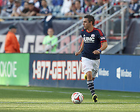 New England Revolution midfielder Diego Fagundez (14) dribbles down the wing.  In a Major League Soccer (MLS) match, the New England Revolution (blue/white) defeated Houston Dynamo (orange), 2-0, at Gillette Stadium on April 12, 2014.