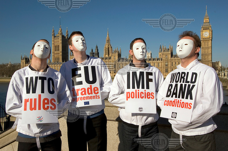 Representatives of the charity Christian Aid wearing masks and straightjackets take part in a Trade Justice demonstration outside the Houses of Parliament, condemning the World Trade Orgnisation (WTO), World Bank, International Monetary Fund (IMF) and the European Union's (EU) trade agreements..