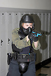 A woman police officer in training holding a paint ball simulated gun clearing a school shooting scenario