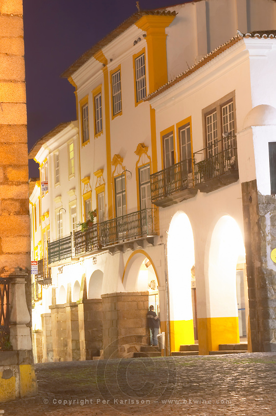 Street view. Cobble stones. Houses and arches on Praca do Giraldo. Evora, Alentejo, Portugal