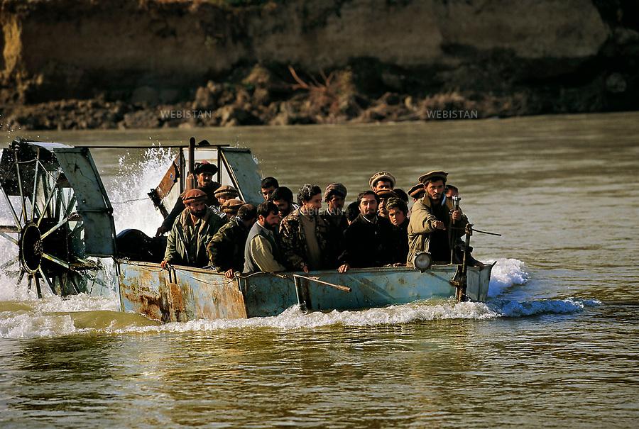 Afghanistan, Dargad. November 2000.<br /> Commandant Massoud, his bodyguards, some of his close collaborators, and Dr. Abdullah, the Afghan Minister of Foreign Affairs cross the Kowkcheh River from Dargard to one of his headquarters in Khvajeh Baha od Din village. They use a boat built from a tractor.<br /> <br /> Afghanistan. Dargad. Novembre 2000.<br /> Travers&Egrave;e, par Massoud et ses hommes, de la rivi&Euml;re Kouktcha, en provenance du village de Dargad, vers un des quartiers g&Egrave;n&Egrave;raux situ&Egrave; dans le village de Khajeh-Bahaoddin. Parmi eux, le docteur Abdollah, ministre des Affaires &Egrave;trang&Euml;res afghan, les gardes du corps et autres proches commandants. Leur moyen de transport : un bateau fabriqu&Egrave; sur les restes d'un tracteur.