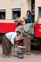 Myanmar, Burma.  Passengers on Train Buying Bananas from Platform Vendors at Kalaw Train Station.