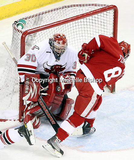 UNO goalie John Faulkner looks to control the puck as Wisconsin's Podge Turnbull closes in. UNO beat Wisconsin 4-1 Friday night at Qwest Center Omaha.  (Photo by Michelle Bishop)