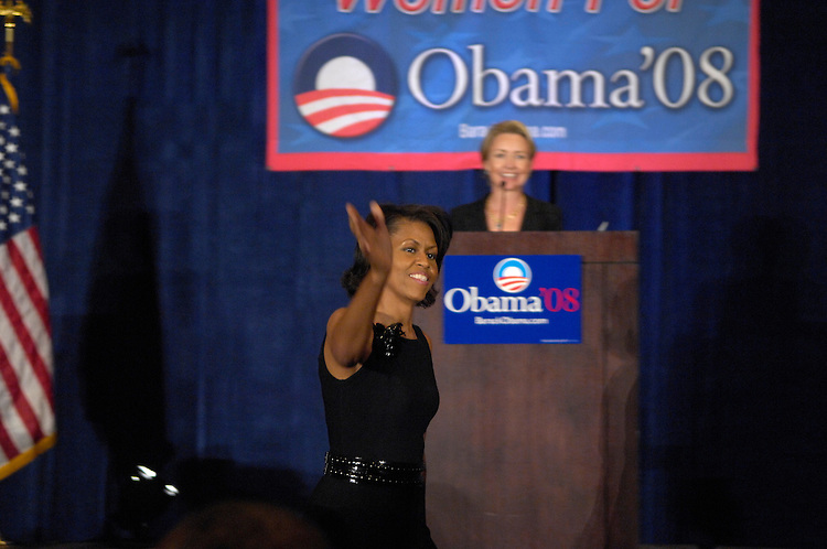 "Michelle Obama enters the room during a fund raiser  ""Women for Obama"" a luncheon benefiting  her husband Senator Barack Obama who is running for President in 2008. In the background is Megan Beyer who introduced Mrs. Obama. The event was held at the Hyatt on at 400 New Jersey Ave in Washington, D.C.."