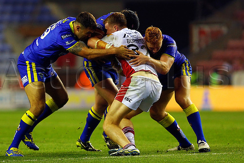 11.09.2014.  Wigan, England.  Super League Rugby. Wigan Warriors versus Warrington Wolves. Joe Burgess of Wigan Warriors holds the Warrington is an equal match for the Warrington Defence