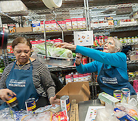 Volunteers check out clients at the West Side Campaign Against Hunger (WSCAH) a supermarket style food pantry on the Upper West Side neighborhood of New York on Friday, December 19, 2014. The clients get to choose their groceries for themselves and their families. In 2014 WSCAH provided food for over 1.1 million meals for nearly 10,000 families. The supermarket-style distribution promotes self-reliance and empowers the clients. (© Richard B. Levine)
