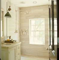 The walk-in shower in the master bathroom is sheathed in walls of travertine