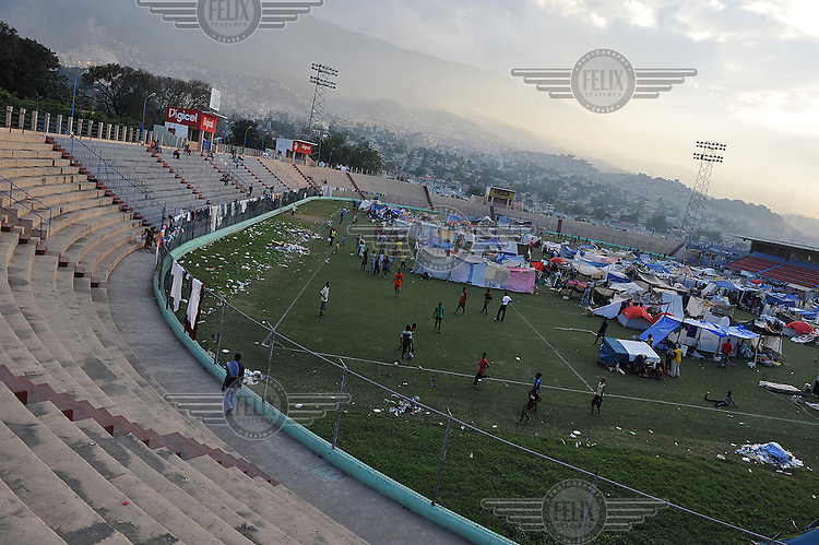 A large number of people who have lost their homes have set up tents on the pitch of the football stadium of Port-au-Prince, one week after an earthquake hit the country. .A 7.0 magnitude earthquake struck Haiti on 12/01/2010. Early reports indicated that more than 100,000 may have been killed and three million affected.