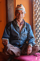 Nepal, Patan.  Museum Guard Sitting on Window Sill with his Radio, wearing his Nepalese hat (topi).