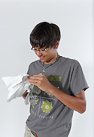 OrigamiUSA 2016 Convention at St. John's University, Queens, New York, USA. Conner Beavers, 17, Charlotte, North Carolina. High school student. OUSA 2016 Convention teacher twice including 2016, OUSA Convention Pro, creator of original origami designs and models. Photo of Conner folding one of his designs.