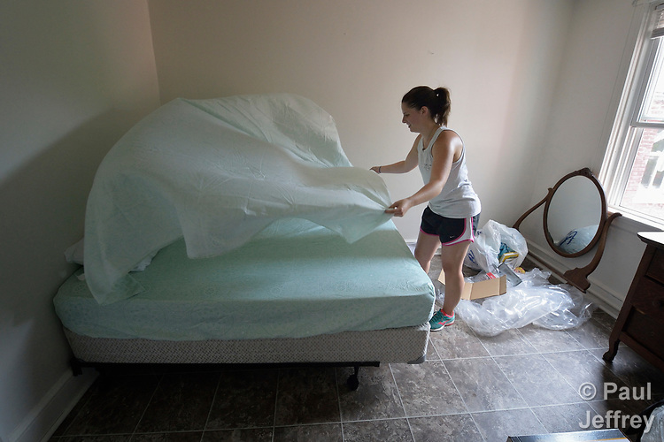 Emilie MacDonald makes a bed in an apartment in Lancaster, Pennsylvania. She is furnishing the apartment of a refugee family about to arrive in the United States. MacDonald works for Church World Service, which resettles refugees in Pennsylvania and other locations in the United States. <br /> <br /> Photo by Paul Jeffrey for Church World Service.