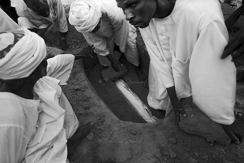 Kalma IDP camp, South Darfur, July 29 2004 Abacar Abdallah, 25 months old, is buried after he died from severe malnutrition, weighing at only 5.2kg, despite desperate last minute efforts by MSF medical staff to save him.