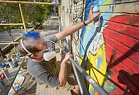 NWA Democrat-Gazette/BEN GOFF @NWABENGOFF<br /> Kenneth Siemens of Bentonville works on his mural on Sunday Sept. 13, 2015 on the side of the building home to Trike Theatre and Peter Pan Cleaners near the Bentonville square. The pop-art style mural was commissioned by Artansas (CQ), an organization promoting public art across the state. Artansas also backed a mural of a fish on S. Main St. in Bentonville that was completed over the summer.