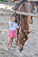 A shy younggirl with horse at the Turtle Bay stables, North Shore, O'ahu.