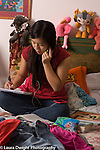 14 year old teenage girl at home in bedroom doing homework talking on cell telephone vertical