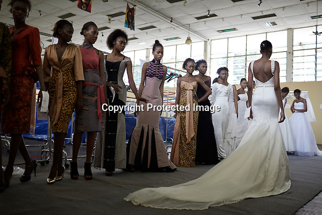 KINSHASA, DRC - JULY 17: Models fit garments for the Nigerian London based designer Yemi Osunkoya a day before Kinshasa Fashion Week on July 17, 2014, at the boxing gym at Shark club in Kinshasa, DRC. Local and invited foreign-based designers showed their collections during the second edition of Kinshasa Fashion week. (Photo by Per-Anders Pettersson)