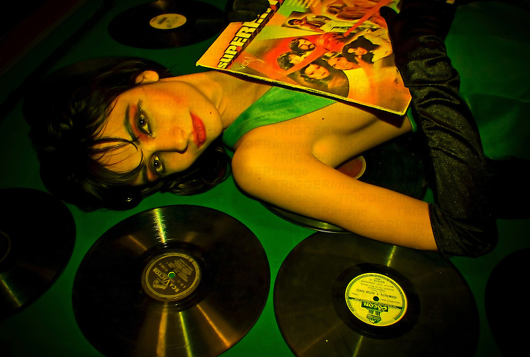 A young woman lying on the floor with records around her