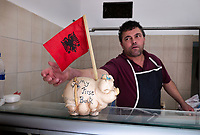 "Albania. Tirana. A butcher in his shop. On the counter, a piggy bank with the written words "" My first bank"" and the Albanian flag. The flag of Albania is a red flag with a silhouetted black double-headed eagle in the center. The red stands for bravery, strength and valor, while the double-headed eagle represents the sovereign state of Albania. The flag was first adopted as the national flag of modern Albania in 1912. Tirana is the capital and most populous city of the Republic of Albania. The city is also the capital of the surrounding county of Tirana, one of 12 constituent counties of the country. 20.5.2018 © 2018 Didier Ruef"