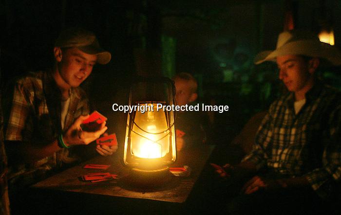 MICHAEL SMITH/WTE..Matt Stallard, age 16, Clayton Combs, age 9, and Thomas Nichols, age 16, play five card draw poker by kerosene lantern at their famiy's chuckwagon on Wild Horse Gulch Monday night.  Cooler weather didn't prevent the boys from playing cards for a few hours however they needed 2 more people to play Texas Hold'em.
