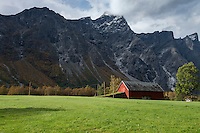 Farm field and barn with mountains of Trollveggen - Troll wall in background, Møre og Romsdal, Norway