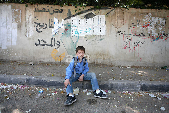A Palestinian boy wearing school uniforms takes a rest in street , in West Bank city of Jericho , on Oct. 11.2010 . Jericho is one of the oldest continuously inhabited cities in the world, with evidence of settlement dating back to 9000 BC,it has a population of over 20,000 Palestinians. Situated well below sea level on an east-west route 16 kilometres (10 mi) north of the Dead Sea, Jericho is the lowest permanently inhabited site on earth . Photo by Eyad Jadallah