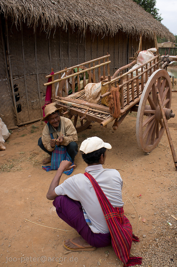 men chatting close to a traditional carriage ,village  Inthein close to  Inle Lake, Shan state,  Myanmar, 2011