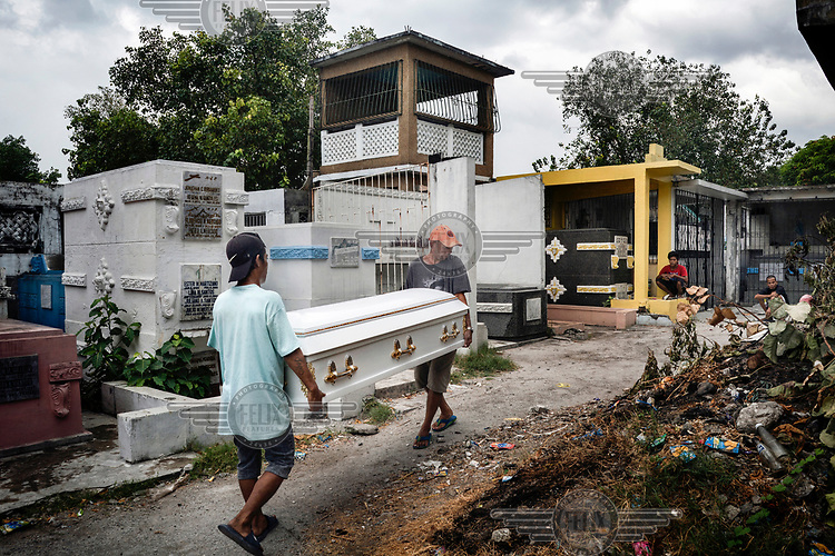 Funeral workers carry the coffin of Glen Balena, 26, during his funeral at Manila North Cemetery. Manila North Cemetery is home to thousands of 'informal settlers' who have built shacks using in and around the mausoleums, crypts and tombs. In comparison to the city's dangerous shantytowns the cemetery is relatively quiet and safe. However, water must be collected from a few public wells and the electricity supply is erratic, usually stolen from mains cables. In the summer the sweltering heat drives people to sleep outside often on top of the tombs.<br /> <br /> Some of the residents live in the crypts and mausoleums of wealthy families, who pay them a stipend to clean and watch over them. Others make a living carving headstones or selling candles to visitors and helping out at funerals as the daily life of the cemetery goes on around the people who live there.