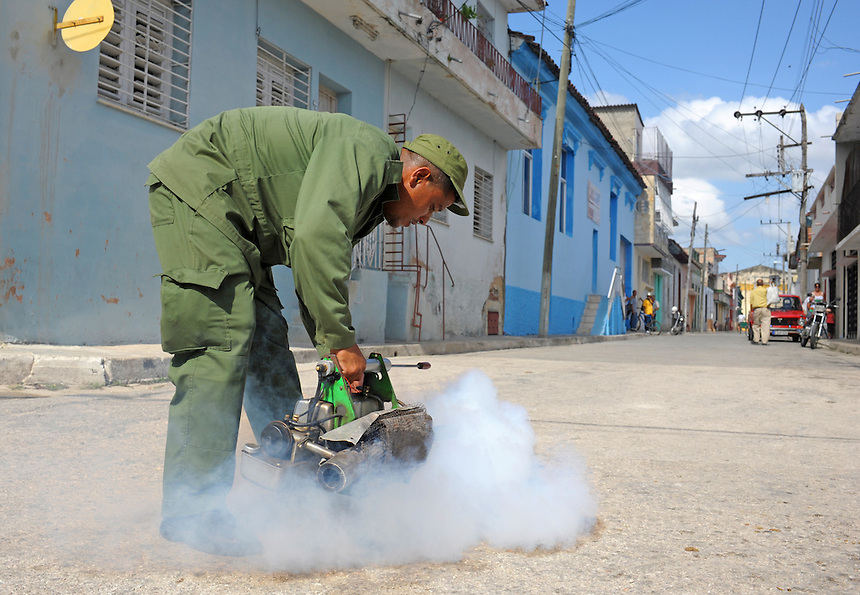 A member of the campana anti-vectorial fills sewers with smoke to fight the Zika virus in Santa Clara, Cuba. MARK TAYLOR GALLERY