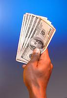 A hand holding $100 bills.