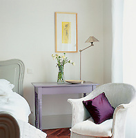 A traditional bedroom decorated in soft grey and off-white. A Lloyd Loom style wicker chair stands next to a baroque style bed from Blanc d'Ivorie. A lavender painted side table and an aubergine cushion provide touches of contrast colour.