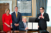 United States President Donald J. Trump holds up the order after signing the last of three Executive Orders concerning financial services at the Department of the Treasury in Washington, DC on April 21, 2017.  From left to right: US Representative Claudia Tenney (Republican of New York) US Senator David Perdue (Republican of Georgia), the President, and US Secretary of the Treasury Steven Mnuchin.<br /> Credit: Ron Sachs / Pool via CNP