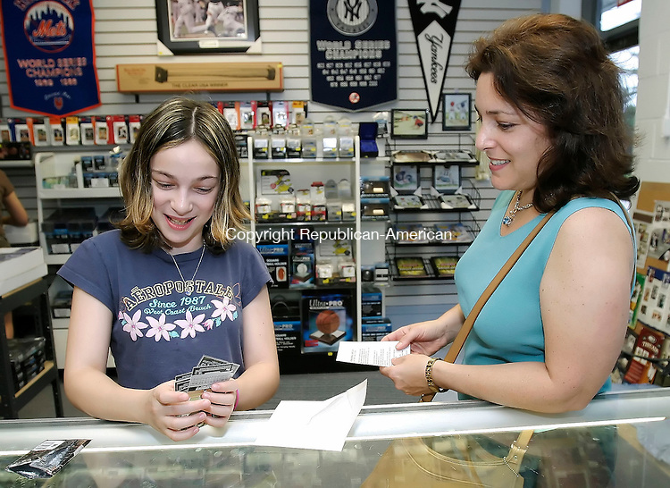 SEYMOUR, CT, 14 June 2006- 061406BZ02-  First-time card buyer Shana Konoval, 11, of Oxford, left, looks through a pack of Topps Co-Signers cards at Ernie's Baseball Cards in Seymour as her mother Judy Konoval, right, watches Wednesday night. Shana, who was rewarded with the cards for getting good grades in school, got a Mickey Mantle number card and a limited edition, #113/150 Paul LoDuca card in the pack.<br /> Jamison C. Bazinet Republican-American
