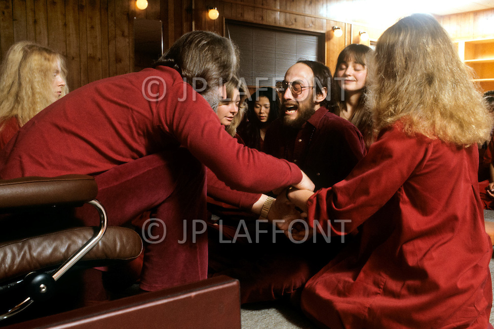 """Wasco, Oregon, January 1984: Swami Anand Teertha Baptizing new members at Rajneeshpuram. The Darshan Ceremony took place every Sunday evening. Swami Anand Teertha was one of the eight """"acharyas"""" ( grand priests) in the world, selected by Bhagwan Rajneesh who had the right to baptize new members. Rajneeshpuram, was an intentional community in Wasco County, Oregon, briefly incorporated as a city in the 1980s, which was populated with followers of the spiritual teacher Osho, then known as Bhagwan Shree Rajneesh. The community was developed by turning a ranch from an empty rural property into a city complete with typical urban infrastructure, with population of about 7000 followers."""